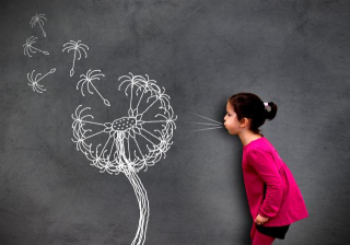S_Little_cute_girl_blowing_dandelion_seeds_on_chalkboard_-_Hope_and_aspirations_concept